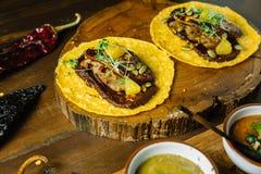 Foie Gras taco tjänade som på träskärbräda med olika såser, och mexikanen torkade chili fotografering för bildbyråer