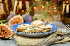 Foie gras on wholewheat bread. With juicy ripe figs served as snacks at a festive celebration with colorful party lights in the background Stock Photo