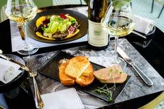 Foie savoureux Gras avec des pains grillés et le verre de vin blanc à un restaur image stock