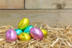 Foil covered Easter eggs in a barn. Foil covered chocolate Easter eggs in a straw nest in a barn Stock Images