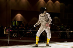 Foil Fencer Ready To Compete. A competitive foil fencer stands ready to begin a fencing bout at a tournament Stock Photography