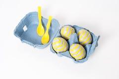 Foil los huevos de Pascua cubiertos del chocolate con las cucharas plásticas en la caja de papel en el fondo blanco Fotos de archivo