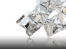 Foil package. On reflect floor and white background Stock Photo
