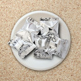 Foil package on white plate Royalty Free Stock Image