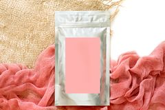 Foil packaging for loose cosmetic products, with a pink sticker, cloth and dried flowers, natural colors. isolate, space for text. royalty free stock photography