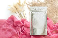 Foil packaging for loose cosmetic products, with a pink sticker, cloth and dried flowers, natural colors. isolate, space for text. stock images
