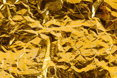 Foil texture golden pattern macro view. Metal crumpled paper with a coloring traces shabby and dust. Decorative Royalty Free Stock Photography