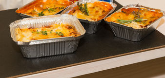 Foil Trays of Cheesy Baked Entrees on Table Royalty Free Stock Images