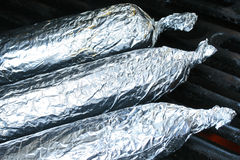 Foil-Wrapped Corn on Grill. Three ears of corn wrapped in foil and cooking on grill Stock Photo