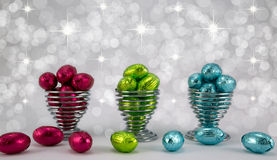 Foil wrapped Easter eggs. Brightly coloured foil wrapped easter eggs in wire eggcups Royalty Free Stock Image