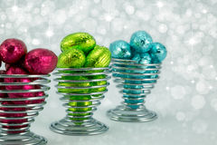 Foil wrapped Easter eggs. Brightly coloured foil wrapped easter eggs in wire eggcups Stock Image