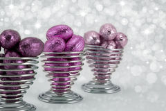 Foil wrapped Easter eggs. Shades of pink foil wrapped easter eggs in wire eggcups.Diffused sparkle background Royalty Free Stock Images