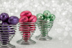 Foil wrapped Easter eggs. Brightly coloured foil wrapped easter eggs in wire eggcups.Diffused sparkle background Royalty Free Stock Photo