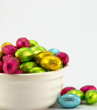 Foil wrapped Easter eggs. Brightly coloured foil wrapped easter eggs in a cream bowl and plain background Royalty Free Stock Photos