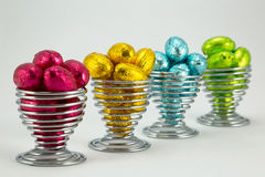 Foil wrapped Easter eggs. Brightly coloured foil wrapped easter eggs in wire eggcups Stock Images