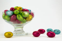 Foil wrapped Easter eggs. Brightly coloured foil wrapped easter eggs in a glass bowl Stock Photos