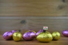Shiny wrapped chocolate Easter eggs and miniature person with sign board for love Easter. Foil wrapped and shiny Easter eggs in yellow gold and pink colors laid Royalty Free Stock Image