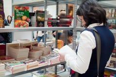 Foire de livre - femme affichant un livre Photos stock