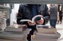 Foire de livre - homme affichant un livre Photographie stock