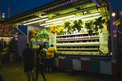 Foire régionale la nuit, jeux sur l'allée centrale photographie stock libre de droits