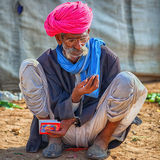 Foire traditionnelle dans Pushkar Homme indien s'asseyant au sol Photographie stock