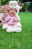 Fokus am asiatischen neugeborenen Baby mit kleinen Schafen der Kostüme im Garten und in der Mutter hält sie Stockfotografie