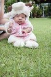 Fokus am asiatischen neugeborenen Baby mit kleinen Schafen der Kostüme im Garten und in der Mutter hält sie Lizenzfreie Stockfotos