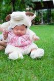 Fokus am asiatischen neugeborenen Baby mit kleinen Schafen der Kostüme im Garten und in der Mutter hält sie Stockbild