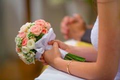 Fokus auf dem Vordergrund Braut, die ihren Hochzeitsblumenstrauß mit Rosen hält Lizenzfreie Stockfotos