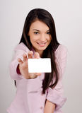 Junge Frau, die eine leere Visitenkarte halten lächelt. Lizenzfreie Stockfotografie