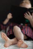 Fokus auf Füßen Lesung des kleinen Jungen Lizenzfreie Stockfotos