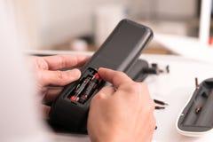 Fokus auf Frauenhand ändert die Fernsteuerungsbatterie, die Reparatur und die Wartung stockfotos