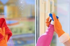 Fokus auf Glasoberfläche Spray für das Säubern in Hände lizenzfreie stockfotografie