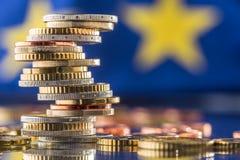 Fokus auf Seil Euroflagge Fünf, 10 und fünfzig Eurobanknoten Münzen gestapelt auf einander i Stockfotografie