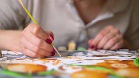 Fokus auf weiblichen Händen mit Maniküremalerei auf Segeltuch mit Zahlen stock footage