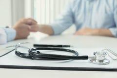 Fokus av medicinska instrument, stetoskopet och doktorn som trycker på PA Arkivbilder