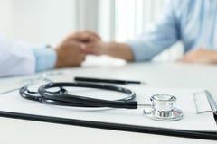 Fokus av medicinska instrument, stetoskopet och doktorn som trycker på PA Arkivfoto