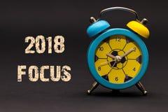 Fokus 2018 geschrieben mit Wecker auf schwarzen Papierhintergrund Stockbilder