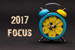 Fokus 2017 geschrieben mit Wecker auf schwarzen Papierhintergrund Lizenzfreie Stockfotos