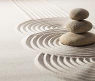 Fokus på att balansera stenar i sand för fortgång i liv arkivfoto