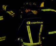 Fokus på söder - afrikanska brandmän i Rosenbauer bunkerkugghjul på natten Royaltyfri Fotografi