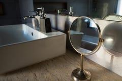 Fokus på spegeln för rund tabell bredvid lyxig vit vask i royaltyfri bild