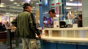 Fokus von den Leuten, die Geld innerhalb des Flughafens austauschen stock footage