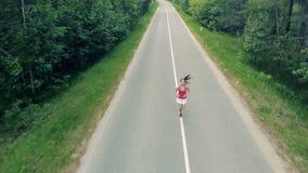 Fokusen flyttar sig i väg från en slank nätt kvinna som joggar i gränden _ arkivfilmer