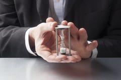 Fokusera i rätt tid ledning med händer som rymmer ett timglas Arkivbild