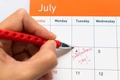 Fokusera på den röda pennmarkeringen på kalendern för 4th Juli som Royaltyfri Bild
