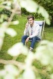 Fokusera på den unga mannen som väntar på telefonen i frodig lövverk Royaltyfri Bild