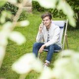 Fokusera på en gullig ung man som utomhus väntar på telefonen Arkivbilder