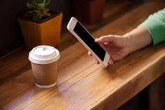 Fokusera på hipsterkvinnan som använder smartphonen med drinken royaltyfria foton
