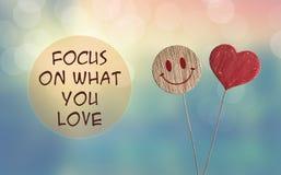 Fokusera på vad du älskar med hjärta och ler emoji arkivbild